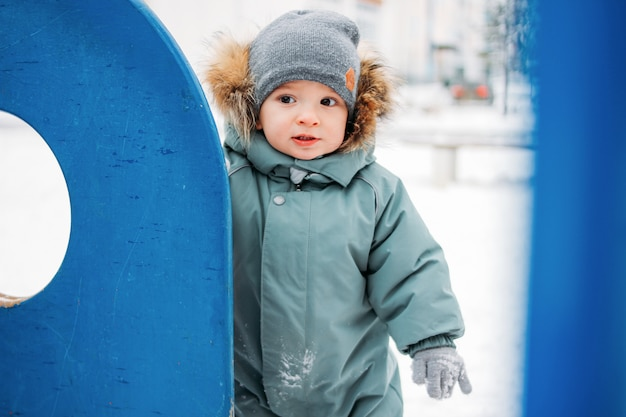 Cute baby boy in warm overall and grey knitted hat in winter street