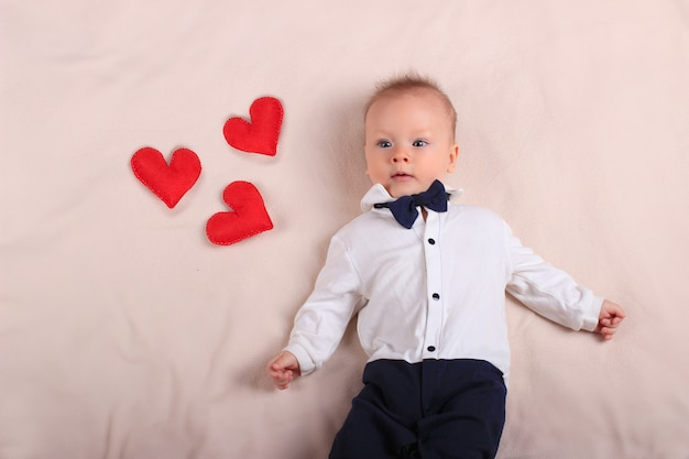 Cute baby boy wearing tuxedo and bow tie with red toy hearts as symbol of mother's day and love with copy space
