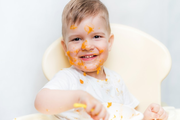 Cute baby boy while eating smeared his face with a pumpkin