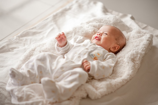 Cute baby boy in a white light bedroom newborn baby is cute. in bedding for children born - images