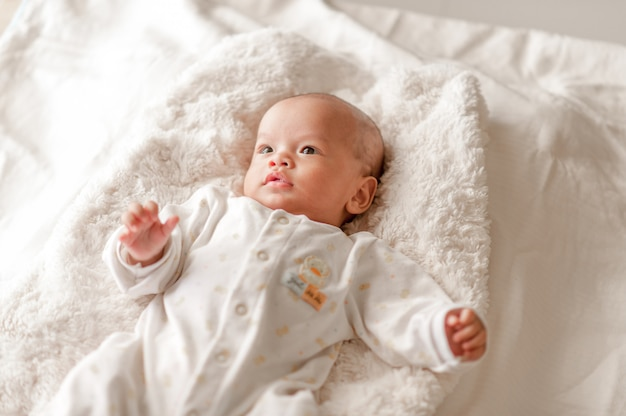 Cute baby boy in a white light bedroom newborn baby is cute.