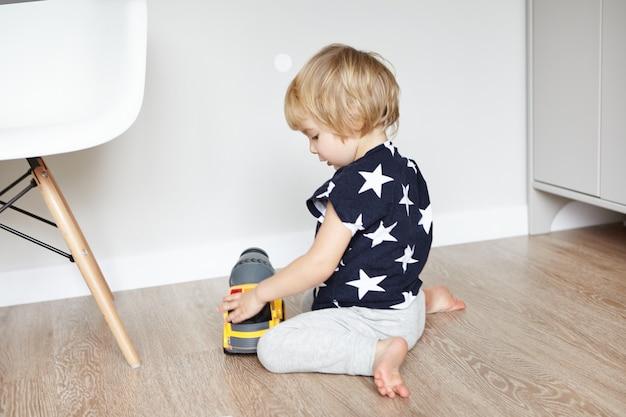彼の寝室の木製の床に座って、彼のお気に入りのおもちゃを押しながら笑みを浮かべて金髪のかわいい男の子。楽しい、黄色のプラスチック製のトラックで遊ぶ幼児。初期の学習。
