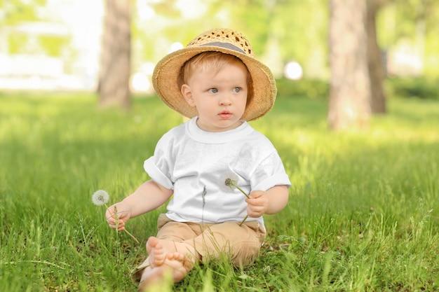 晴れた日に緑豊かな公園でタンポポとかわいい男の子