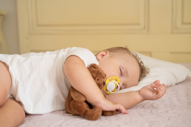 Cute baby boy with nipple sleeping on bed at home child hugging teddy bear