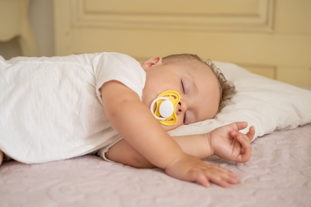 Cute baby boy with nipple sleeping on bed at home