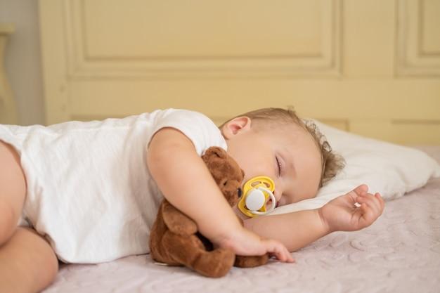 테디 베어를 껴안고 집에서 침대에서 자고 젖꼭지와 귀여운 아기
