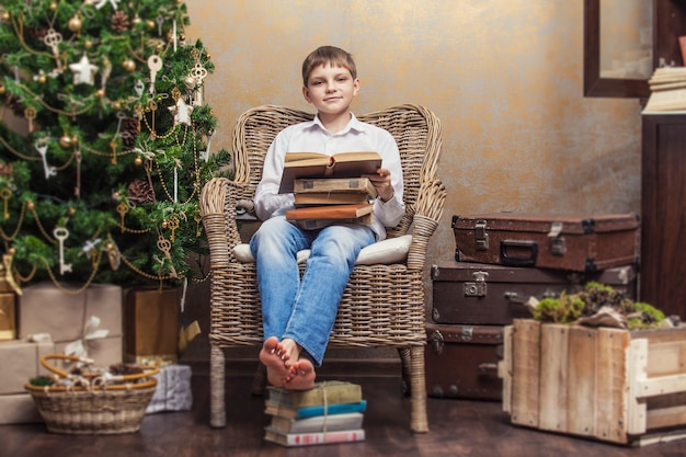 Cute baby in a chair reading a book in a christmas retro interior