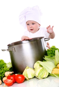 Cute baby chef with big pot and vegetables