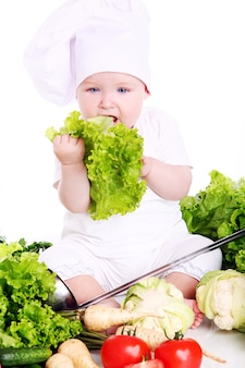 Cute baby chef with vegetables