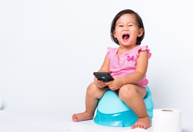 Cute baby child girl education training to sitting on blue chamber pot