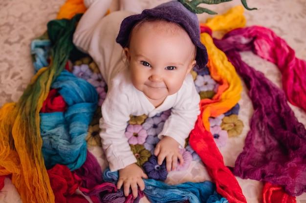 かわいい赤ちゃん。ベルフラワーハットの頭の上で目を開けて子供新生児笑顔