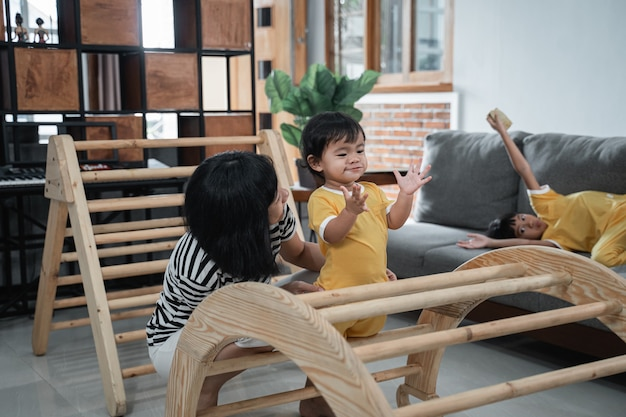 Cute baby clapping hands with his mother while playing in the house