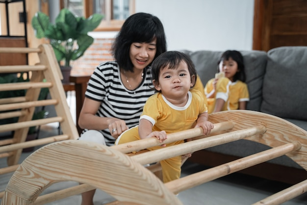 Cute baby climbing pikler climbing toys with his mother while playing together in the house
