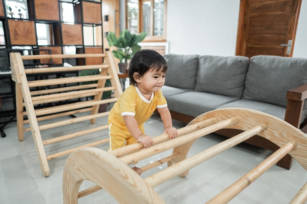 Cute baby climbing on pikler triangle toys in the living room