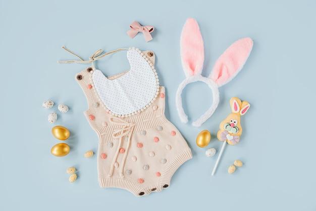 Милый детский костюм пасхальный заяц. вязаный боди, ушки зайчика с пасхальными яйцами и конфетами на синем фоне. концепция праздника. плоская планировка, вид сверху
