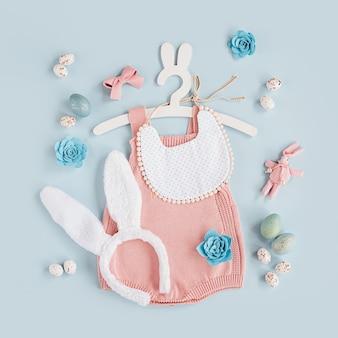Милый детский костюм пасхальный заяц. вязаное боди с пушистыми ушками зайчика, пасхальными яйцами и конфетами на синем фоне. концепция праздника. плоская планировка, вид сверху