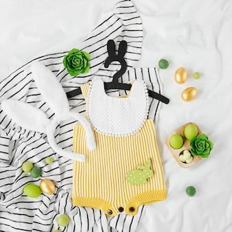 Милый детский костюм пасхальный заяц. вязаное боди с пушистыми заячьими ушками, пасхальными яйцами и украшением на кровати. концепция праздника. плоская планировка, вид сверху