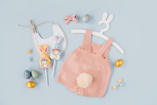 Милый детский костюм пасхальный заяц. вязаное боди с пушистым хвостиком зайчика, пасхальными яйцами и конфетами на синем фоне. концепция праздника. плоская планировка, вид сверху