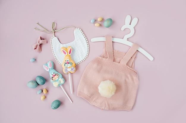Милый детский костюм пасхальный заяц. вязаное боди с пушистым хвостиком зайчика, пасхальными яйцами и конфетами на розовом фоне. концепция праздника. плоская планировка, вид сверху