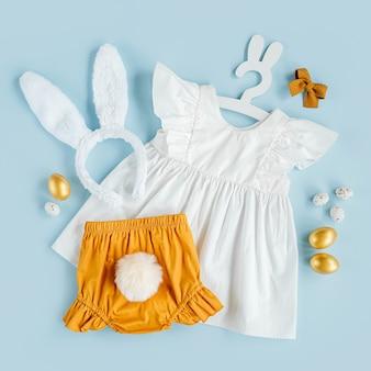 Милый детский костюм пасхальный заяц. белое платье, шорты с пушистым хвостом и ушками кролика с пасхальными яйцами и конфетами на синем фоне. концепция праздника. плоская планировка, вид сверху