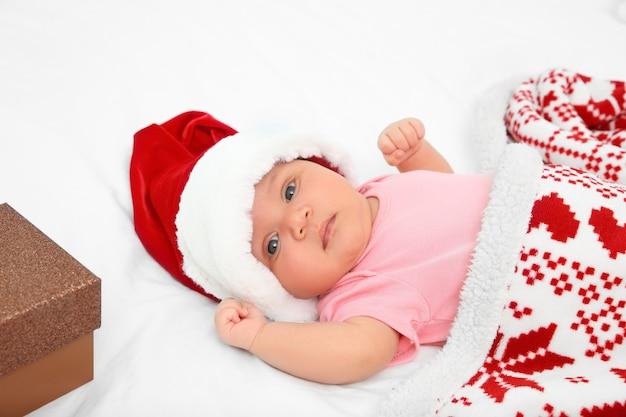 Милый ребенок, покрытый одеялом, лежа на кровати