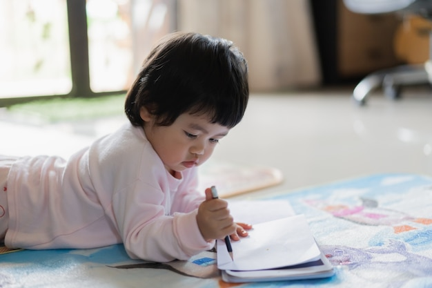 Cute baby drawing on the notebook on the floor