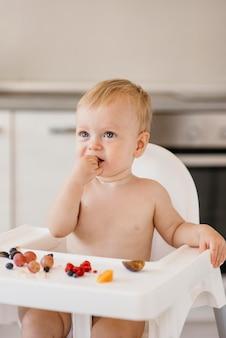 Bambino sveglio che mangia da solo