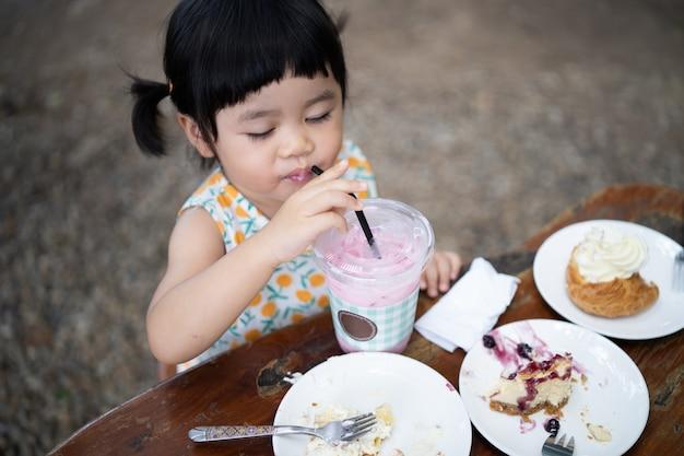 ケーキを食べて、カフェのテーブルに座っているかわいい赤ちゃん
