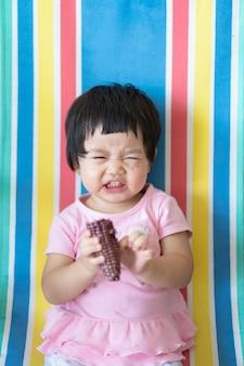 집에서 옥수수를 먹는 귀여운 아기