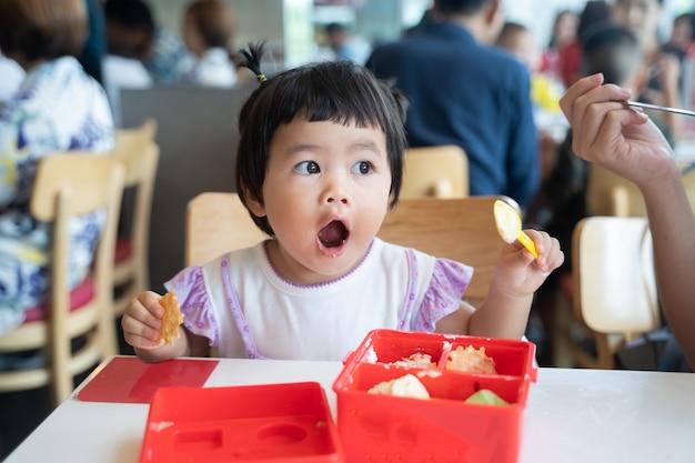 Милый ребенок ест мороженое в ресторане
