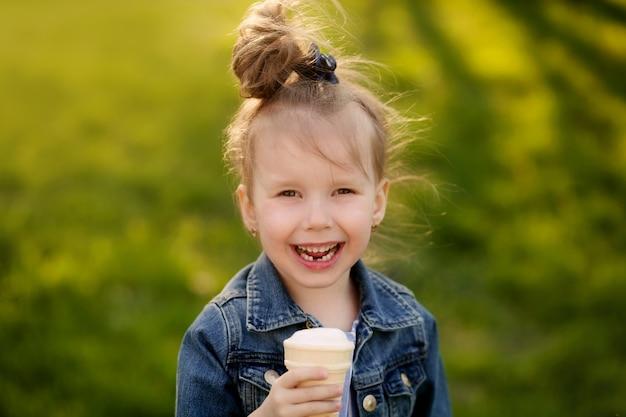 Милый ребенок ест мороженое на открытом воздухе в парке
