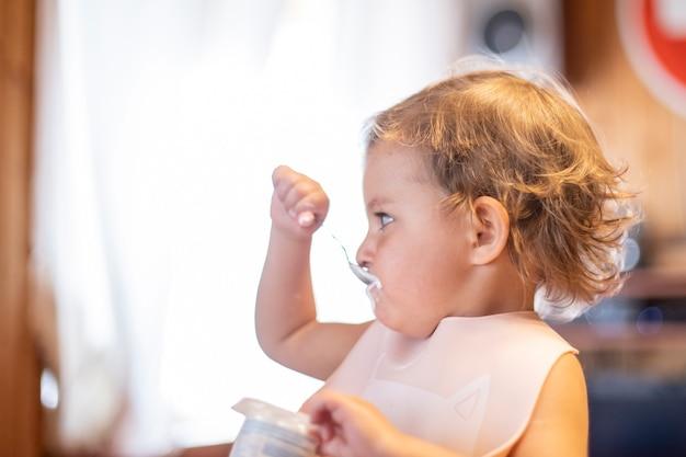Милый ребенок ест йогурт с ложкой сам. очаровательный малыш обедает. голодный ребенок