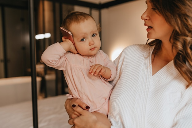 Cute baby in gently pink home clothes is holding phone while her mother hugs her on background of bed.