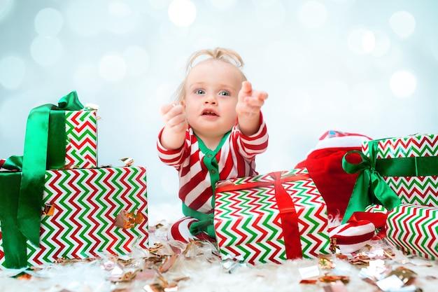 Neonata sveglia 1 anno di età vicino al cappello di babbo natale in posa su sfondo natalizio. seduto sul pavimento con la palla di natale. stagione delle vacanze.