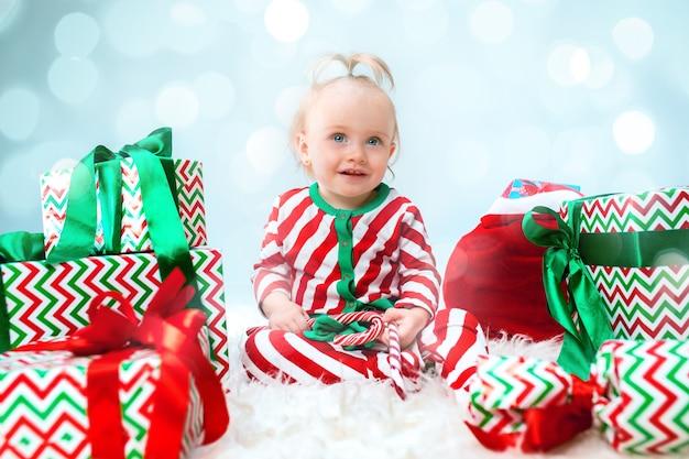 Neonata sveglia 1 anno di età vicino al cappello della santa che propone sopra il natale con la decorazione. seduto sul pavimento con la palla di natale