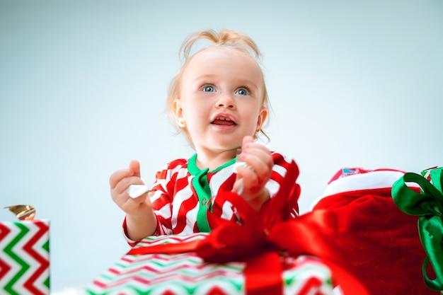 Neonata sveglia 1 anno di età vicino al cappello della santa che propone sopra il natale
