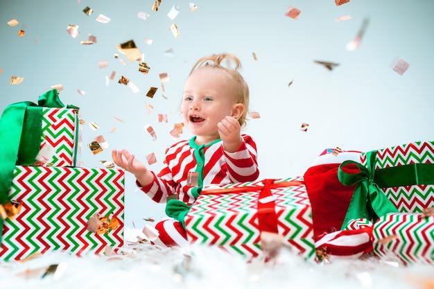 Cute baby girl 1 year old near santa hat posing over christmas