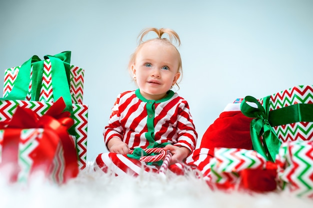 Cute baby girl 1 year old near santa hat posing over christmas