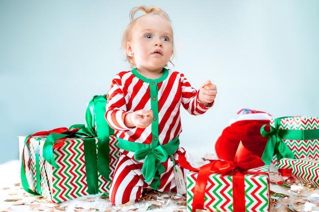 クリスマスの背景にポーズをとってサンタ帽子に近い1歳のかわいい赤ちゃん女の子。クリスマスボールが付いている床に座っています。連休シーズン。