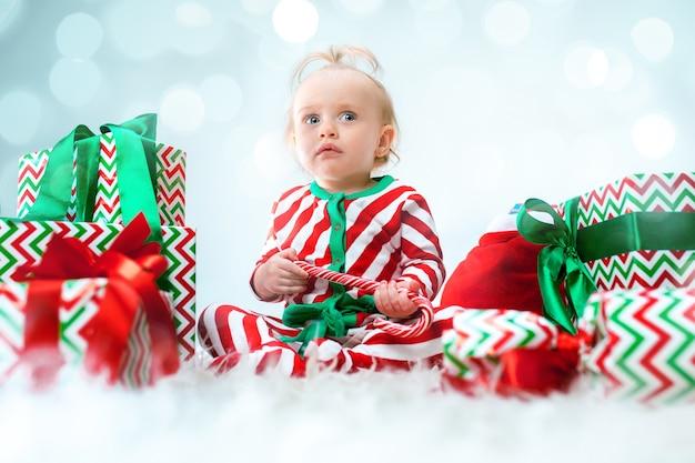 クリスマスにポーズをとってサンタの帽子の近くに1歳のかわいい女の赤ちゃん
