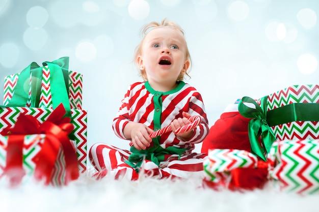 Симпатичная девочка 1 года возле шляпы санта-клауса позирует на рождество