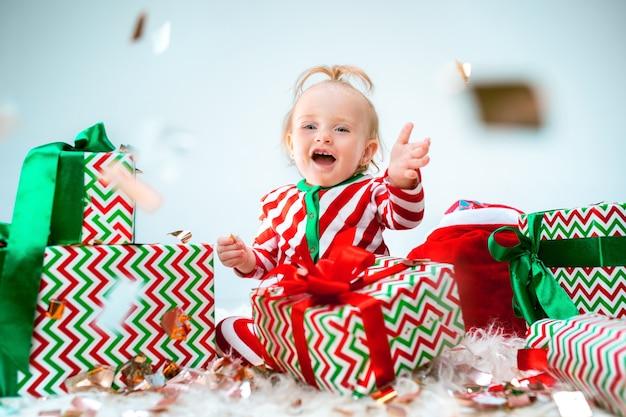크리스마스에 포즈를 취하는 산타 모자 근처 1 살 귀여운 아기 소녀
