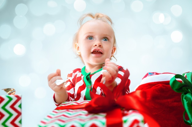 Cute baby girl 1 year old near santa hat sitting on floor with christmas ball
