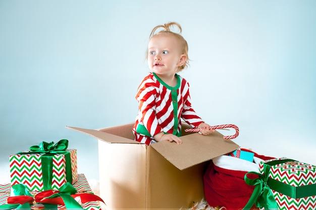 Neonata sveglia 1 anno di età seduto nella casella su sfondo natalizio. vacanza, celebrazione, concetto di bambino