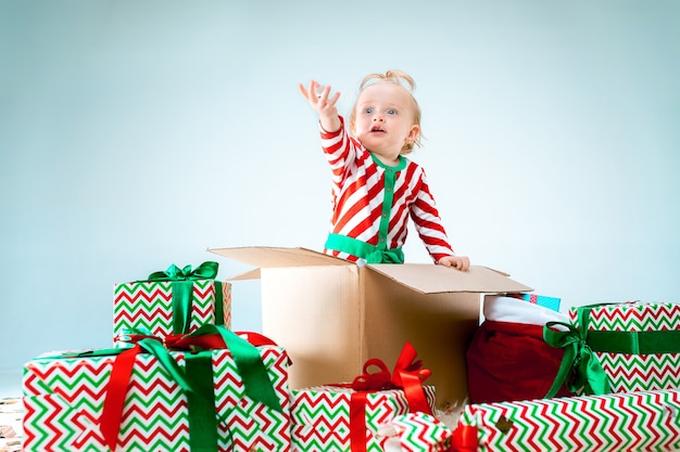 Cute baby girl 1 year old sitting in box over christmas background. holiday, celebration, kid concept