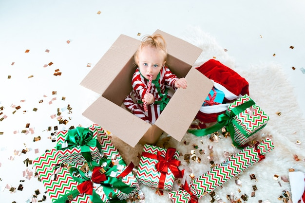 Cute baby girl 1 year old sitting in box over christmas decoration background. holiday, celebration, kid concept