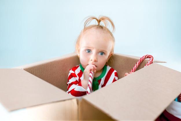 クリスマスの背景の上のボックスに座っているかわいい赤ちゃん女の子1歳。休日、お祝い、子供のコンセプト