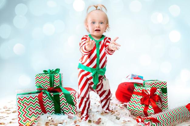 Cute baby girl 1 anno di età che indossa il cappello della santa in posa su sfondo natalizio. in piedi sul pavimento con la palla di natale. stagione delle vacanze.