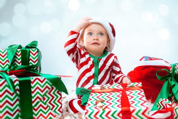 Cute baby girl 1 anno di età che indossa il cappello della santa in posa su decorazioni natalizie con doni. seduto sul pavimento con la palla di natale