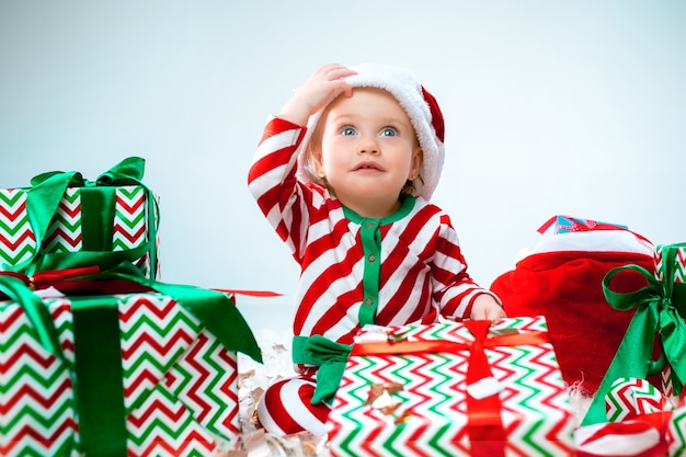 Cute baby girl 1 year old wearing santa hat posing over christmas decorations